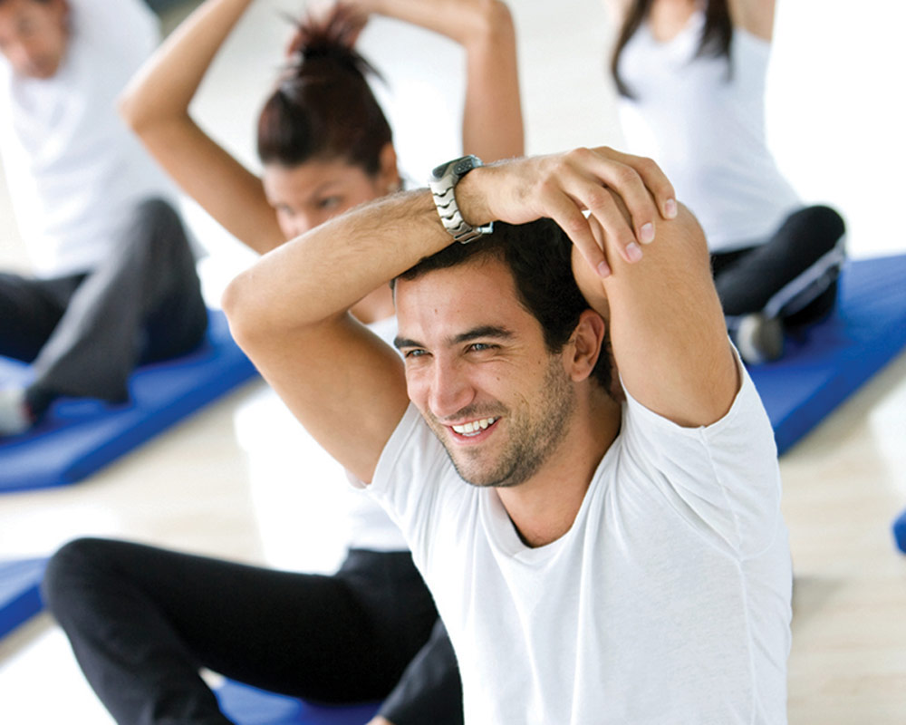 Smiling man in exercise class stretching